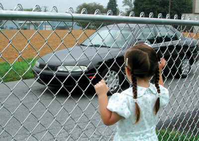 girl by a galvanized chain link fence